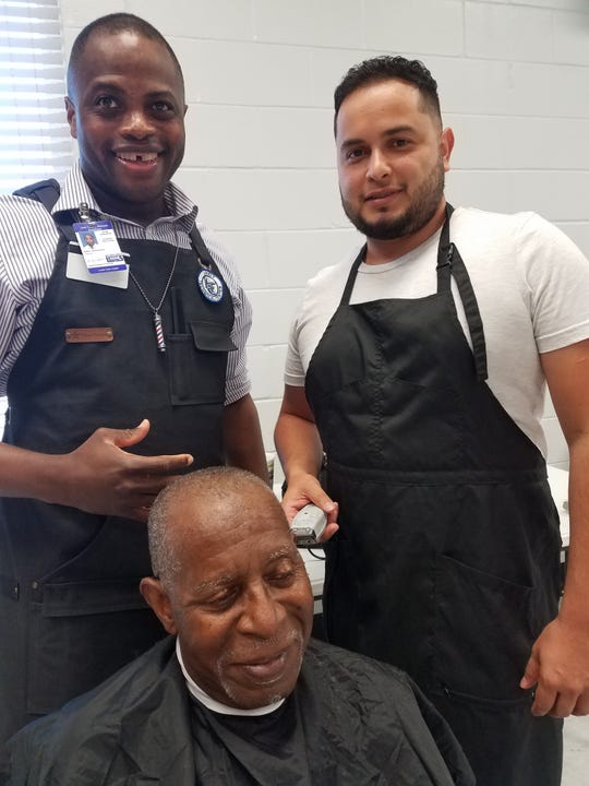 Mahir Rutherford is the instructor and enthusiastic cheerleader for a group of seven young barbers from Lively Technical Center.