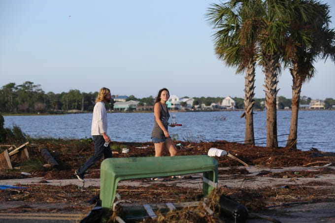 Andrew Purvis, 29, left and Tiara Walker, 21, walk toward the St. George Island bridge to see the debris that cover it after Hurricane Michael Thursday, Oct. 11, 2018.