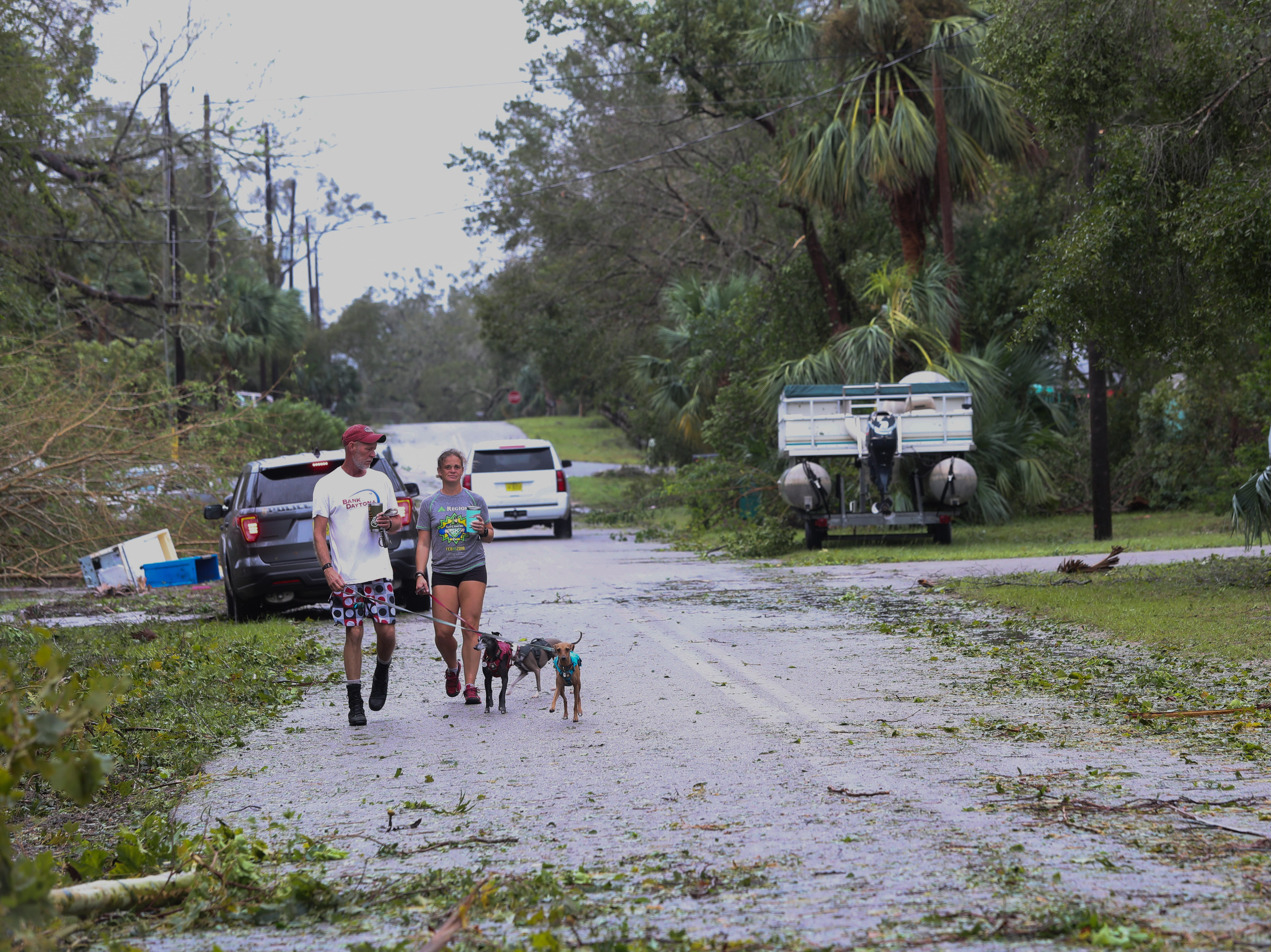 Bobby and Eden Keene walk their dogs after Hurricane Michael in Apalachicola, Fla. Wednesday, Oct. 10, 2018.