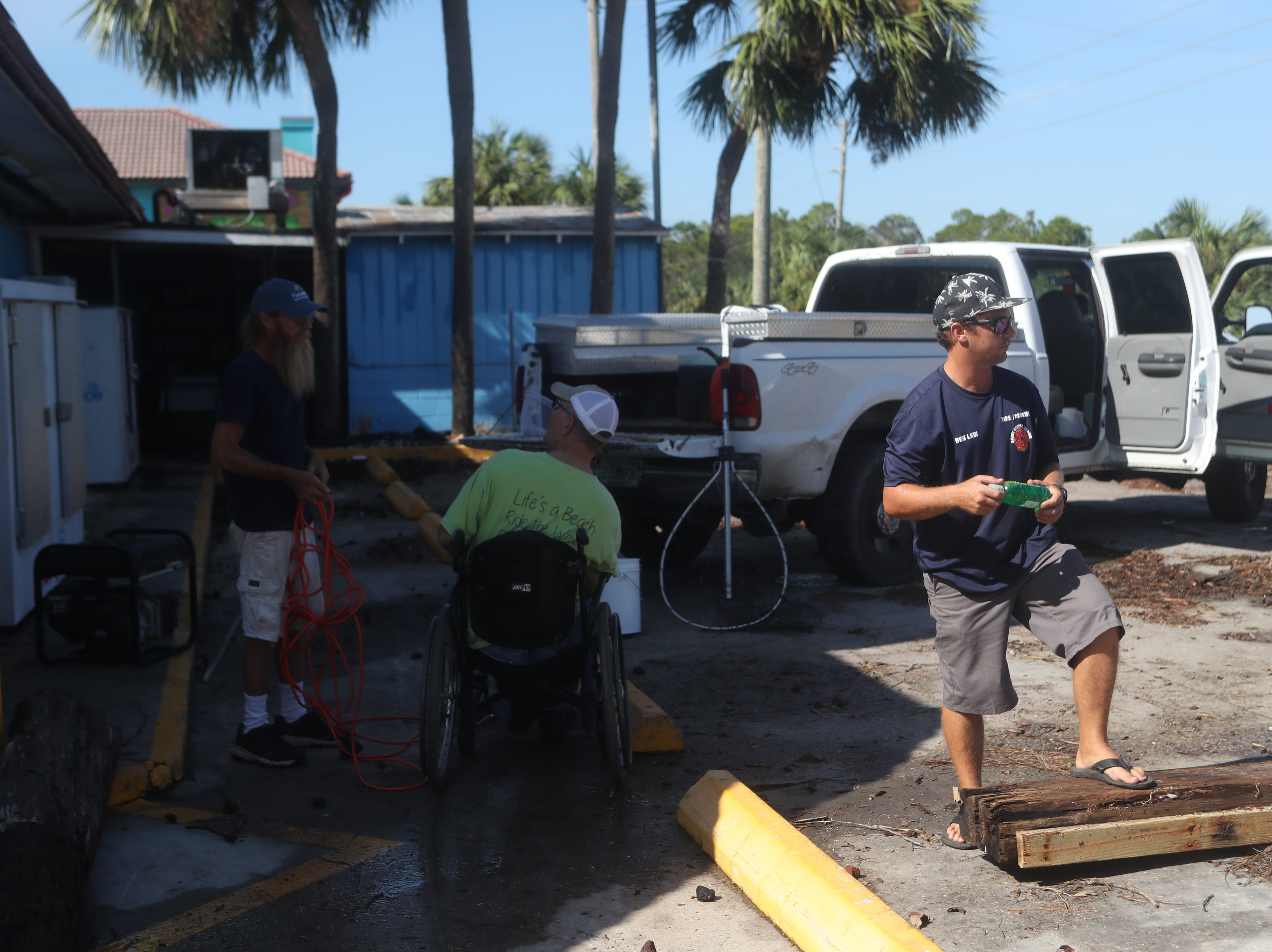 Ben Law helps to clean up around Piggly Wiggly Xpress on St. George Island, Fla. after Hurricane Michael Thursday, Oct. 11, 2018.