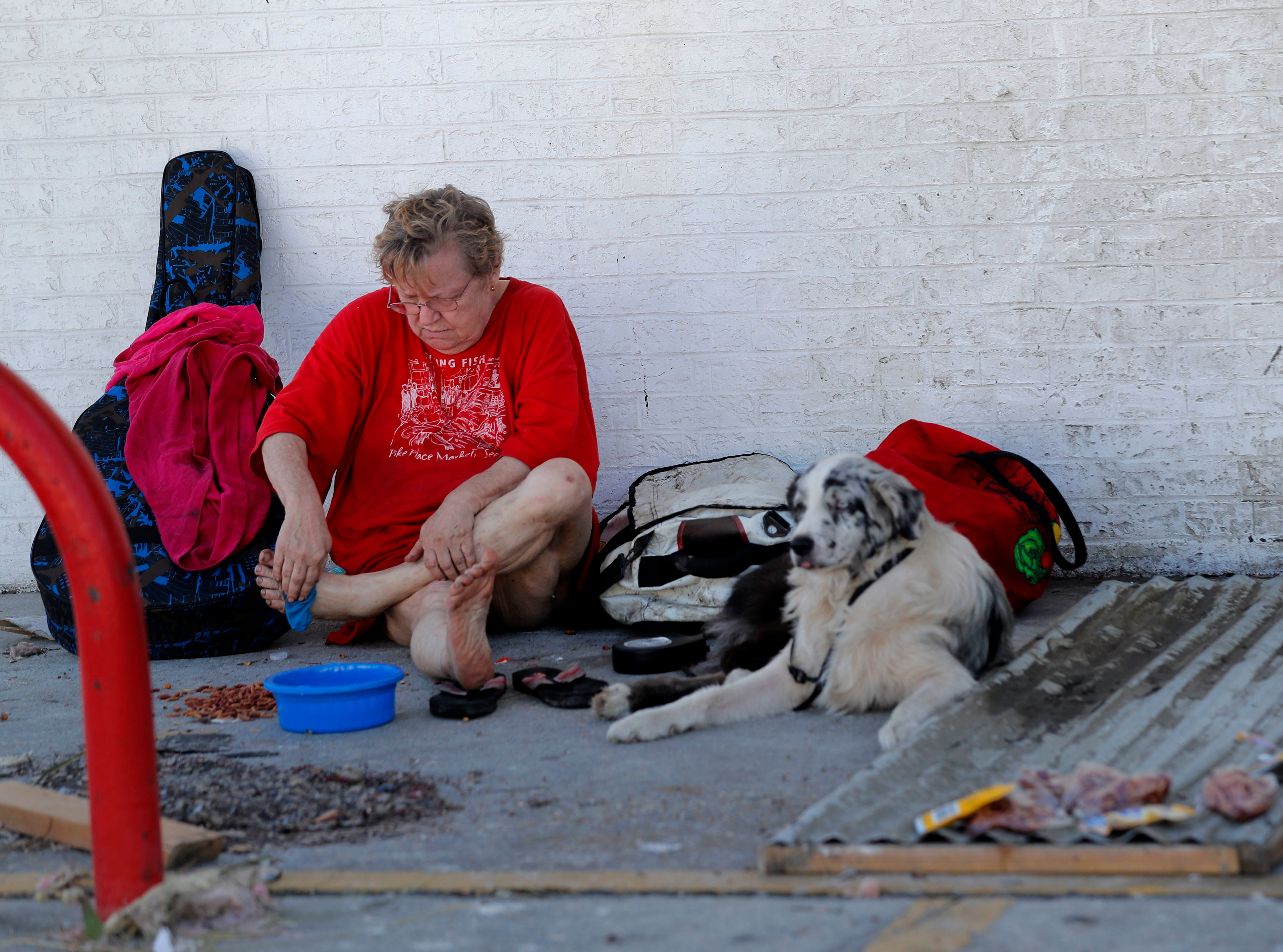 Robin Retzloff who rode out Hurricane Michael in her now destroyed home, sits in front of a heavily damaged convenience store with her dog Markie, the aftermath of Hurricane Michael in Mexico Beach, Fla., Thursday, Oct. 11, 2018. Her husband is in a hospital and she has not been able to reach him, so she has nowhere to go. (AP Photo/Gerald Herbert)