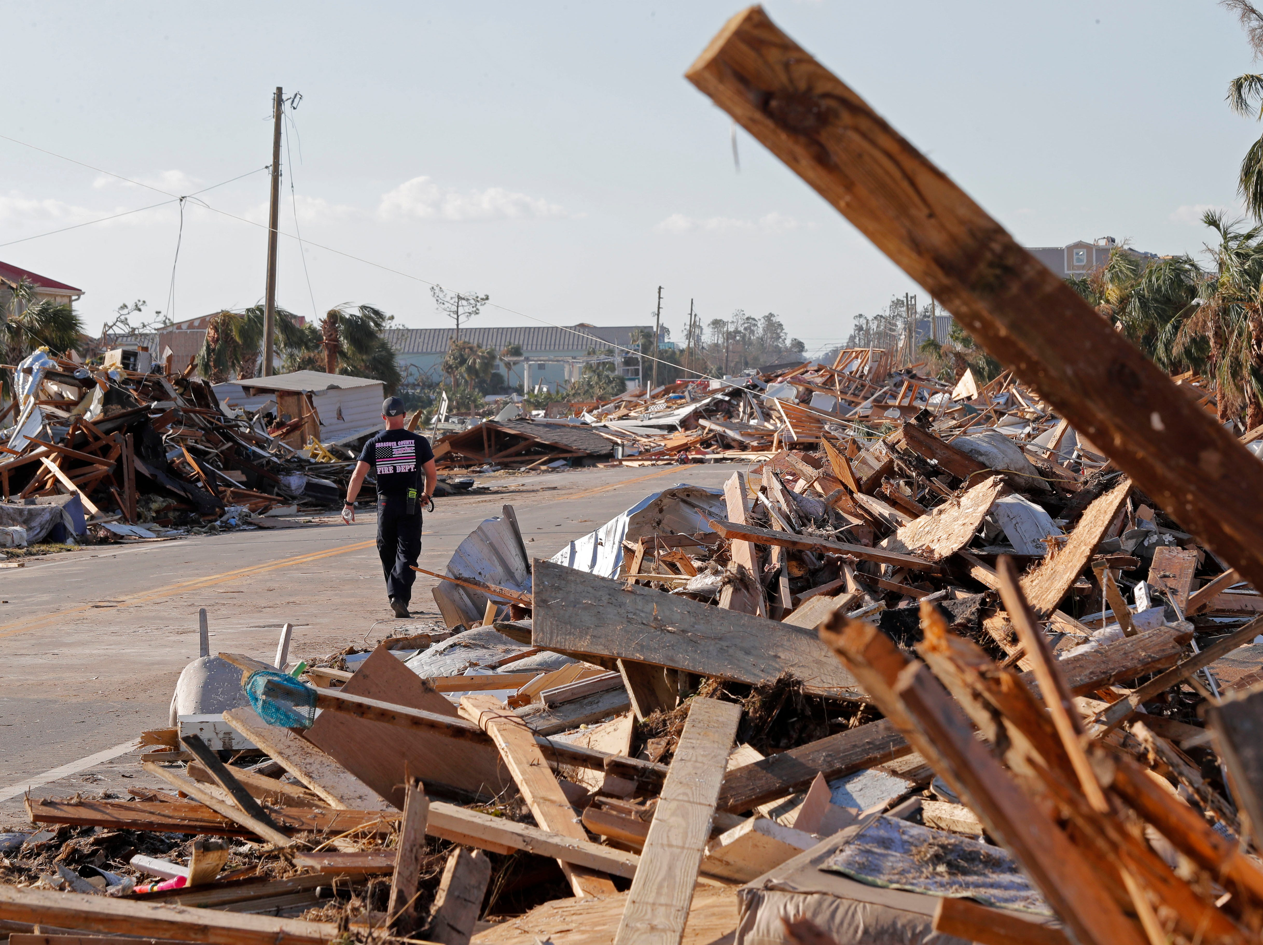 Logan Brisson of the Sarasota County Fire Dept. strike team, walks past debris in the aftermath of Hurricane Michael in Mexico Beach, Fla., Thursday, Oct. 11, 2018. The devastation inflicted by Hurricane Michael came into focus Thursday with rows upon rows of homes found smashed to pieces, and rescue crews began making their way into the stricken areas in hopes of accounting for hundreds of people who may have stayed behind. (AP Photo/Gerald Herbert)