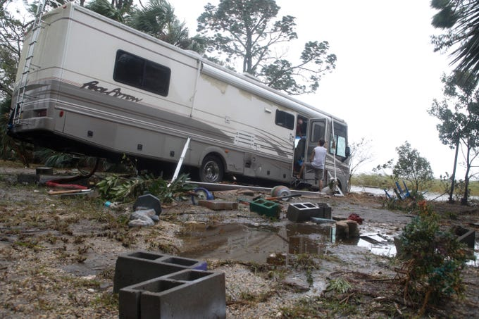 Dana Allen and Jeremy Stanley discuss the damage done to Allen's RV along U.S. Highway 98 after Hurricane Michael in Apalachicola, Fla. Wednesday, Oct. 10, 2018.