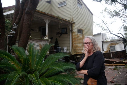 Day McGee surveys the damage on her friend Mary SinnockÕs houses along U.S. Highway 98 in Apalachicola, Fla. McGee was taking care of SinnockÕs house while she is away in Indianapolis taking care of a friend. McGee got SinnockÕs cat out of the house last night.