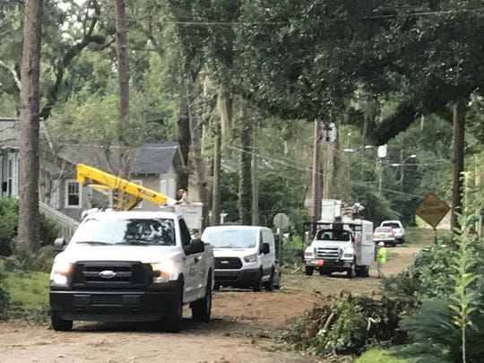 Crews from Lakeland Electric work to repair transmission line damage at the intersection of Ingleside and Pine in Lafayette Park while an Asplundh truck waits to get through