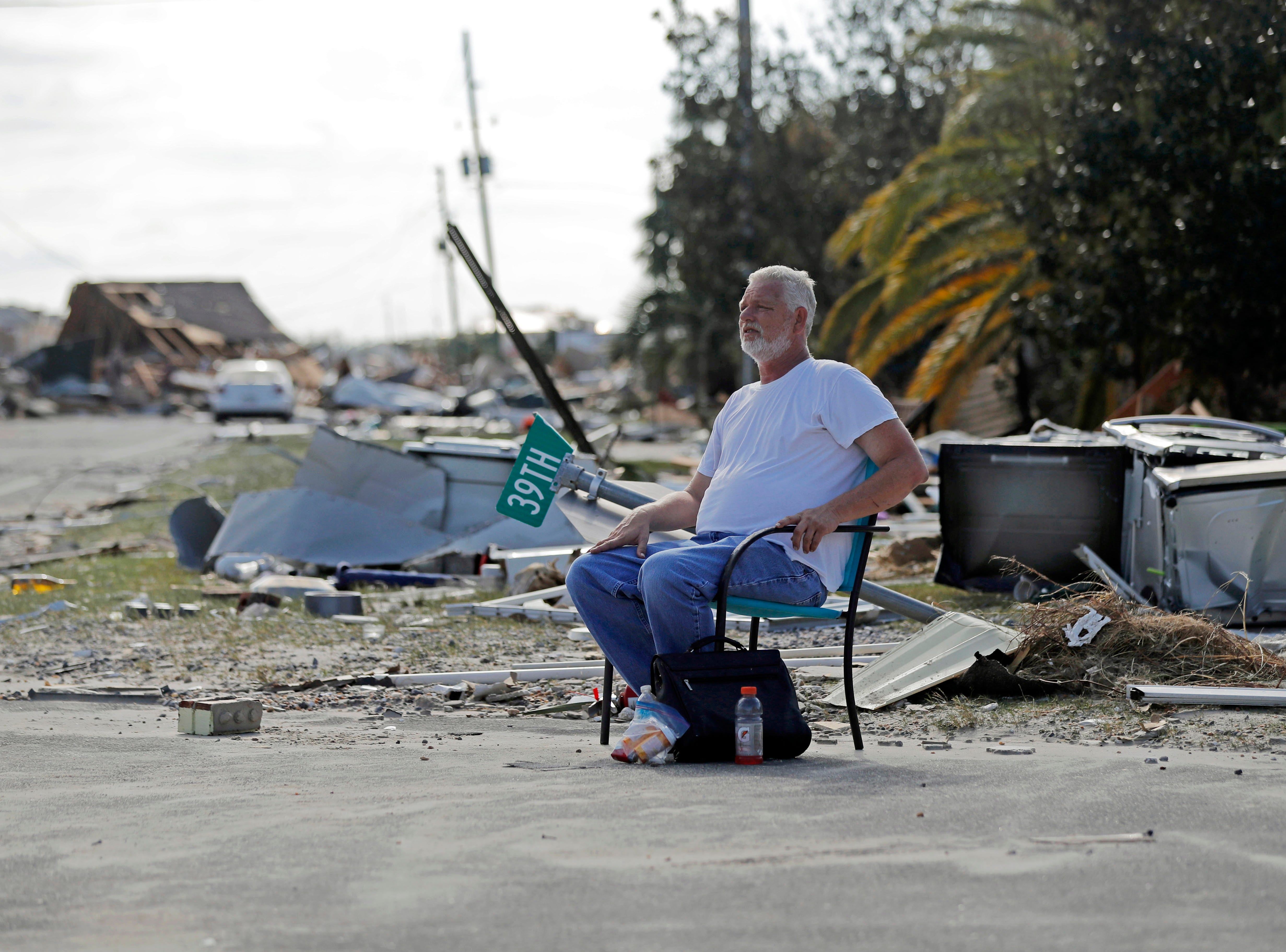 Resident Tony Feller, who stayed in Mexico Beach, Fla., during Hurricane Michael, sits in a chair amidst the destruction, Thursday, Oct. 11, 2018. (AP Photo/Gerald Herbert)