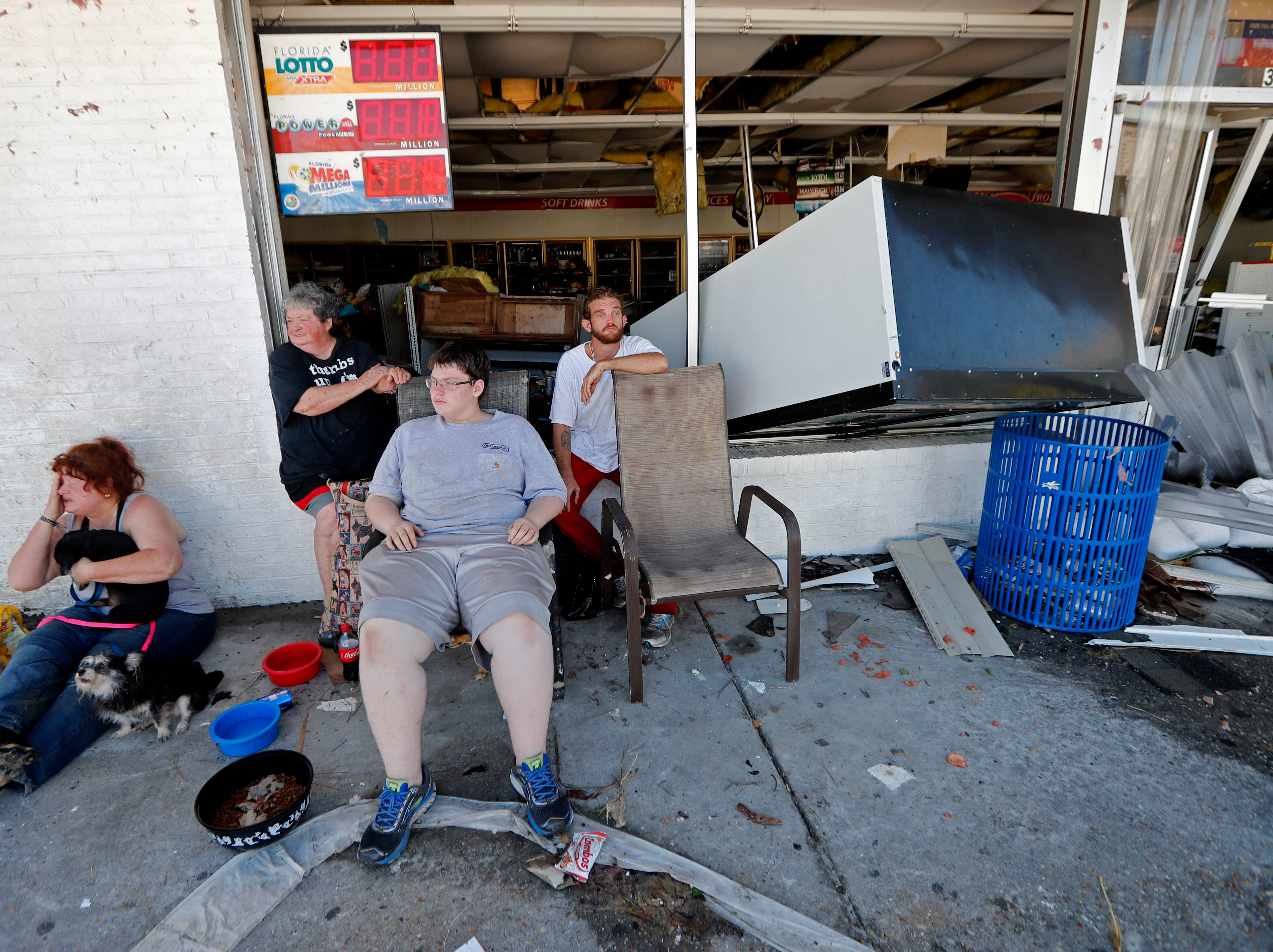 Dawn Vickers, left, her mother Patsy Vickers, son Ryder Vickers, and friend Robert Brock, right, who rode out Hurricane Michael in their now-destroyed home, sit in front of a damaged convenience store with nowhere to go, in Michael's aftermath, in Mexico Beach, Fla., Thursday, Oct. 11, 2018. Their house floated away from its foundation in the storm and they escaped the water by wading through a window. (AP Photo/Gerald Herbert)