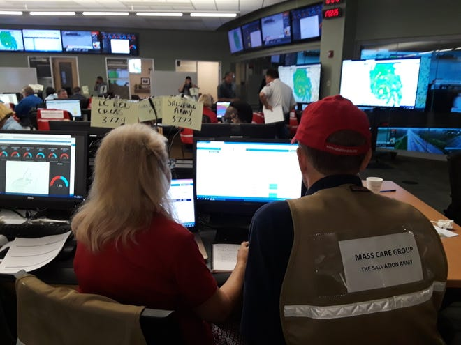 Margo Armistead, left, and Gene Kelly, right, of the Salvation Army get updates from the Emergency Operations Center in Tallahassee.