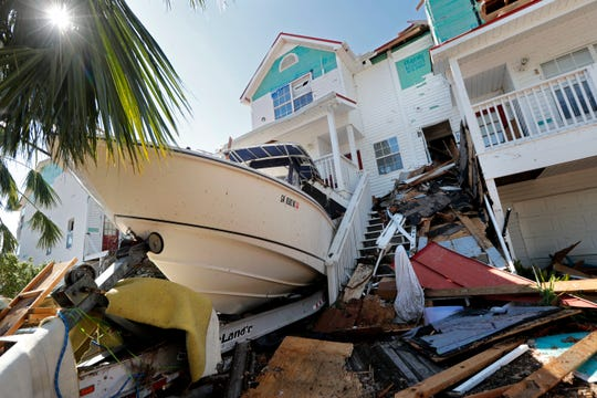 A boat sits lodged into a home in the aftermath of Hurricane Michael in Mexico Beach, Fla., Thursday, Oct. 11, 2018. (AP Photo/Gerald Herbert)