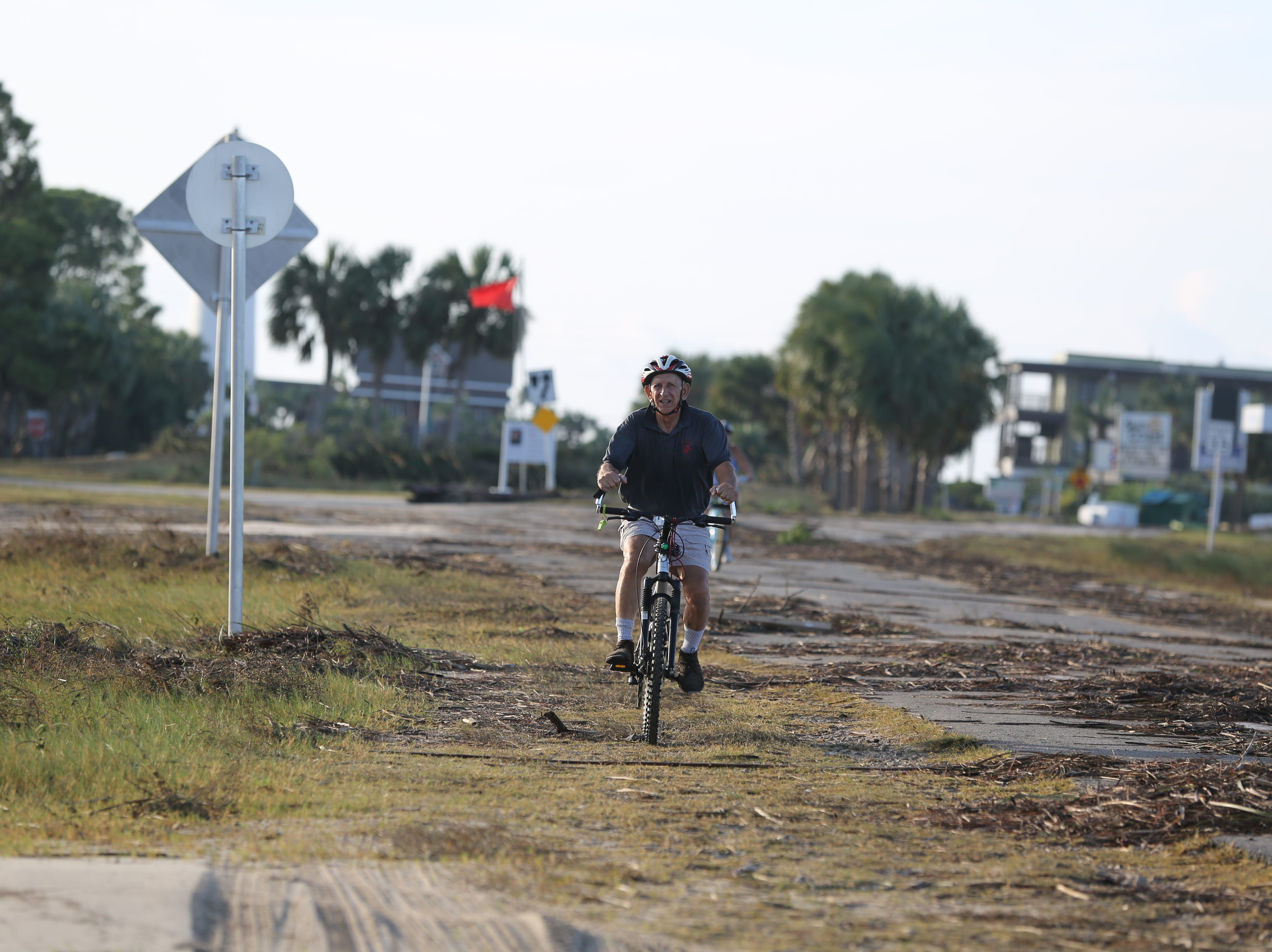 Bob Bogusky bikes toward the St. George Island bridge to survey the debris and damage done during Hurricane Michael Thursday, Oct. 11, 2018.