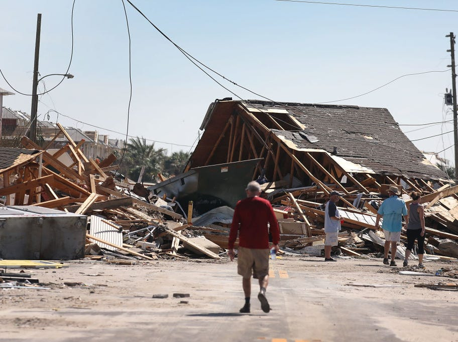 MEXICO BEACH, FL - OCTOBER 11:  People walk along a street blocked by a building  after Hurricane Michael passed through the area on October 11, 2018 in Mexico Beach, Florida.  The hurricane hit the panhandle area with category 4 winds causing major damage.  (Photo by Joe Raedle/Getty Images)