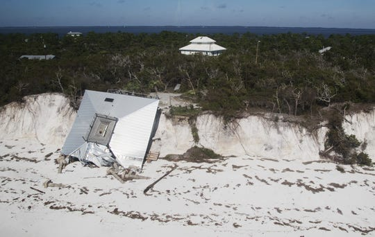 "The remains of the beachfront house on Dog Island built in 1969 by Florida Gov. LeRoy Collins. His grandson hopes the family can salvage the pine floors of the secluded home, which was cherished as a refuge. The home of Bradlee Shanks, which weathered the storm, is visible above the treetops on the ""Mountain"" area of the Franklin County barrier island. Photo by KINFAY MOROTI/THE NEWS-PRESS"