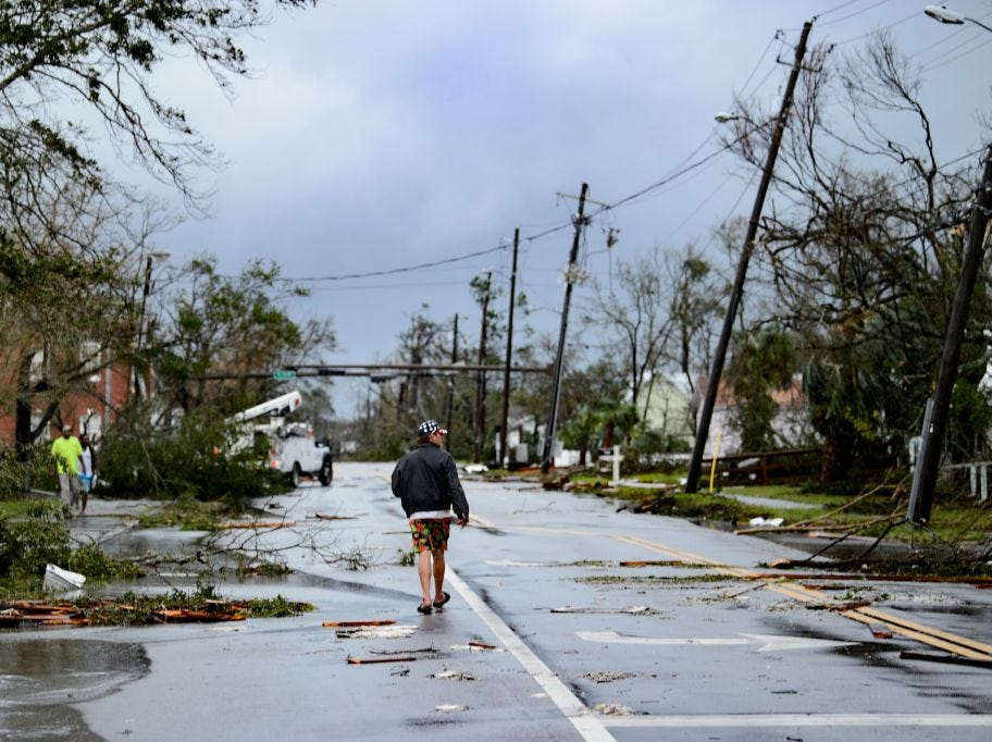 """TOPSHOT - A man walks down the street after Hurricane Michael made landfall on October 10, 2018 in Panama City, Florida. - Michael slammed into the Florida coast on October 10 as the most powerful storm to hit the southern US state in more than a century as officials warned it could wreak """"unimaginable devastation."""" Michael made landfall as a Category 4 storm near Mexico Beach, a town about 20 miles (32kms) southeast of Panama City, around 1:00 pm Eastern time (1700 GMT), the National Hurricane Center said. (Photo by Brendan Smialowski / AFP)        (Photo credit should read BRENDAN SMIALOWSKI/AFP/Getty Images)"""