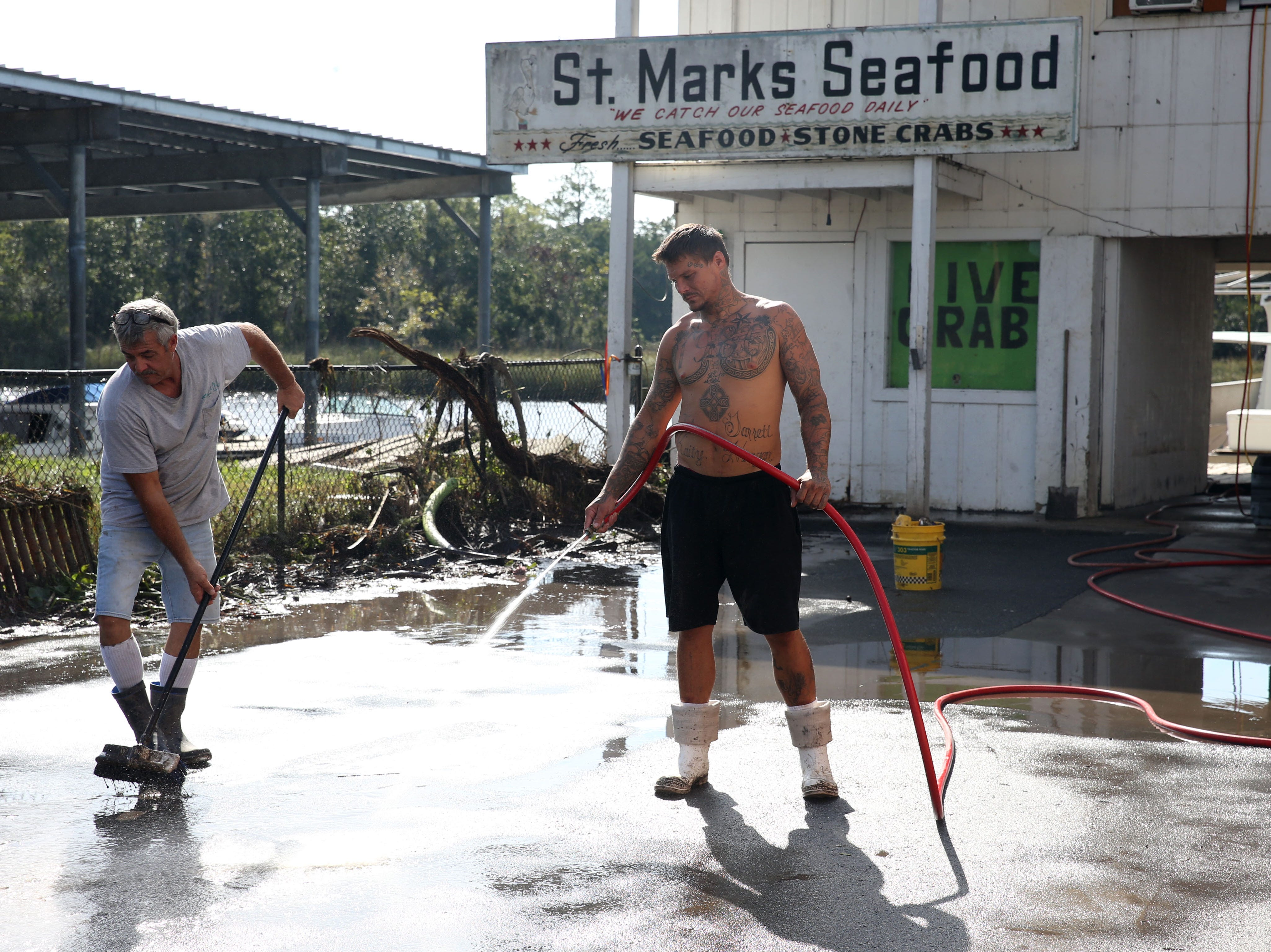 In St. Marks, Fla. on Thursday, Oct. 11, 2018 St. Marks Seafood employees work to remove the river sludge that blankets the ground after Hurricane Michael tears through the panhandle.