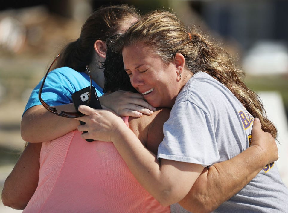 MEXICO BEACH, FL - OCTOBER 11:  Elizabeth Hanson (R) and her daughter, Emaly Hanson hug their neighbor Cindy Clark as they become emotional after dealing with their homes that were heavily damaged when Michael passed through the area on October 11, 2018 in Mexico Beach, Florida.  The hurricane hit the panhandle area with category 4 winds causing major damage.  (Photo by Joe Raedle/Getty Images)