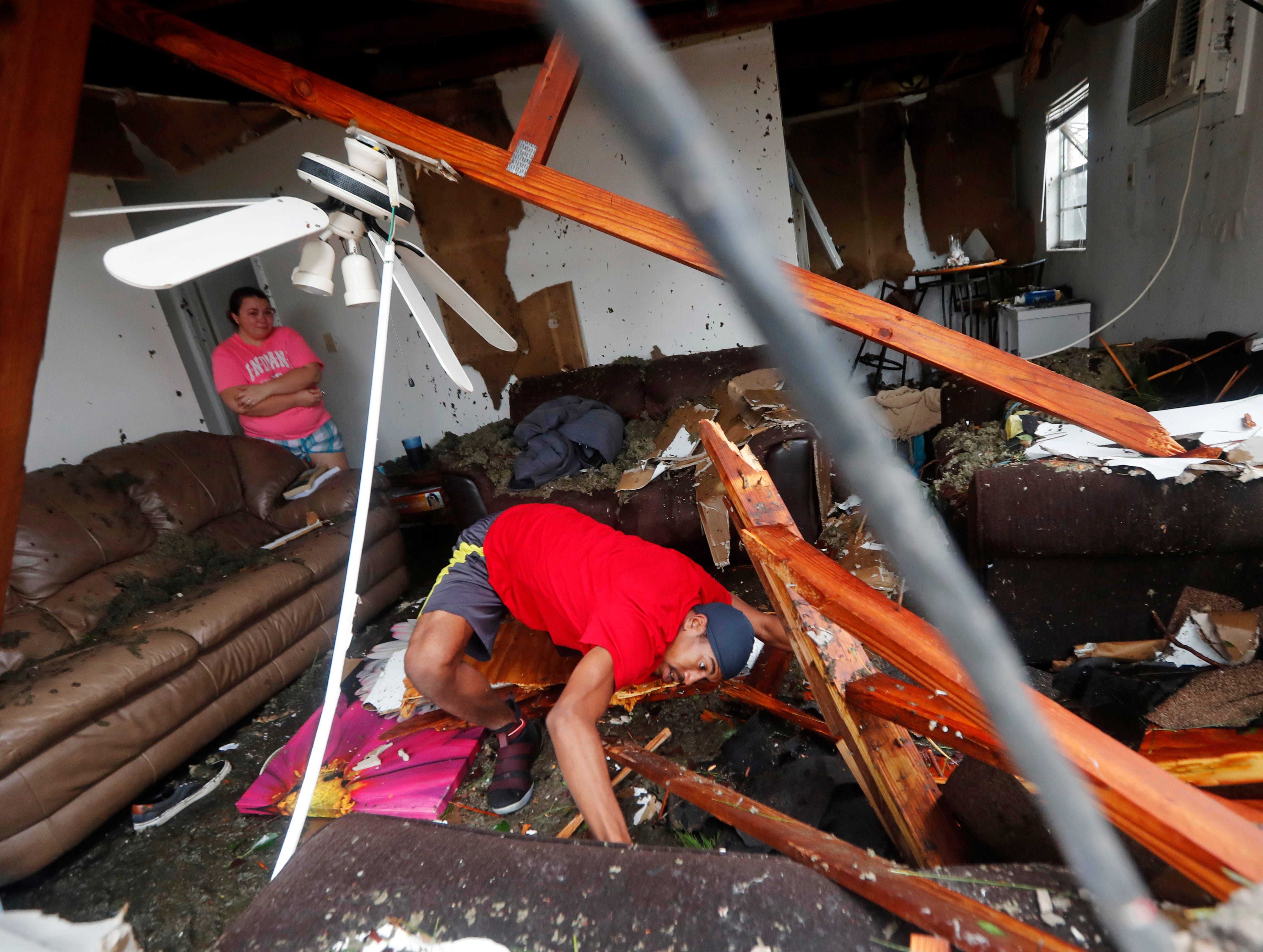 Dorian Carter looks under furniture for a missing cat after several trees fell on their home during Hurricane Michael in Panama City, Fla., Wednesday, Oct. 10, 2018. Supercharged by abnormally warm waters in the Gulf of Mexico, Hurricane Michael slammed into the Florida Panhandle with terrifying winds of 155 mph Wednesday, splintering homes and submerging neighborhoods. (AP Photo/Gerald Herbert)