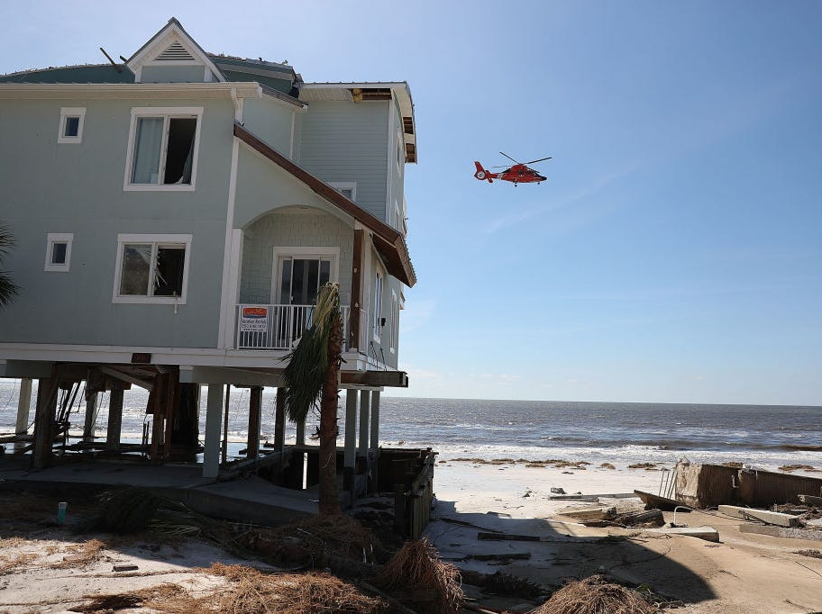 MEXICO BEACH, FL - OCTOBER 11:  A Coast Guard helicopter passes over a damaged home and the foundation of where a home once stood (to the right) before it was blown away by Hurricane Michael as it passed through the area on October 11, 2018 in Mexico Beach, Florida.  The hurricane hit the panhandle area with category 4 winds causing major damage.  (Photo by Joe Raedle/Getty Images)