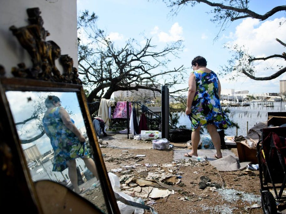Teresa Sheffield walks out of the remains of her second floor apartment in the aftermath of Hurricane Michael October 11, 2018 in Panama City, Florida. - Residents of the Florida Panhandle woke to scenes of devastation Thursday after Michael tore a path through the coastal region as a powerful hurricane that killed at least two people. (Photo by Brendan Smialowski / AFP)        (Photo credit should read BRENDAN SMIALOWSKI/AFP/Getty Images)