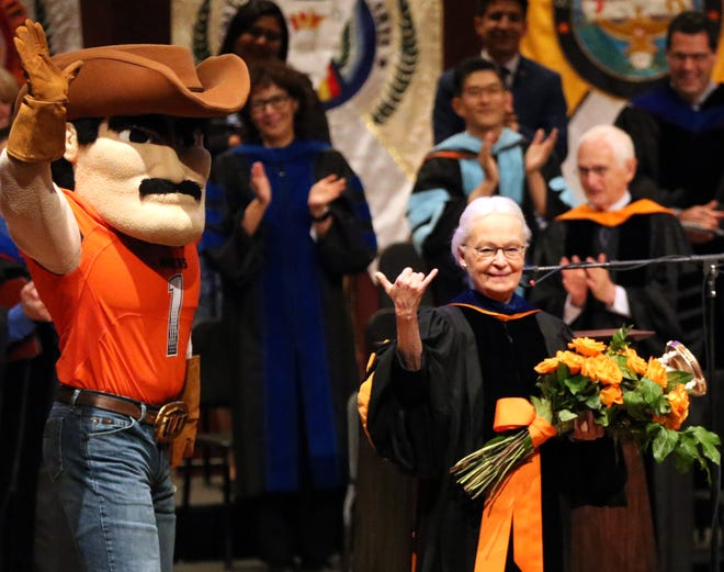 UTEP president Diana Natalicio waves the pick axe sign while receiving a surprise bouquet of flowers form Paydirt Pete at the end of her remarks at the 2018 Fall Convocation at UTEP Thursday on the UTEP campus. Natalico gave an account of the events of the past year plus a synopsis of her 30-year tenure as university president.