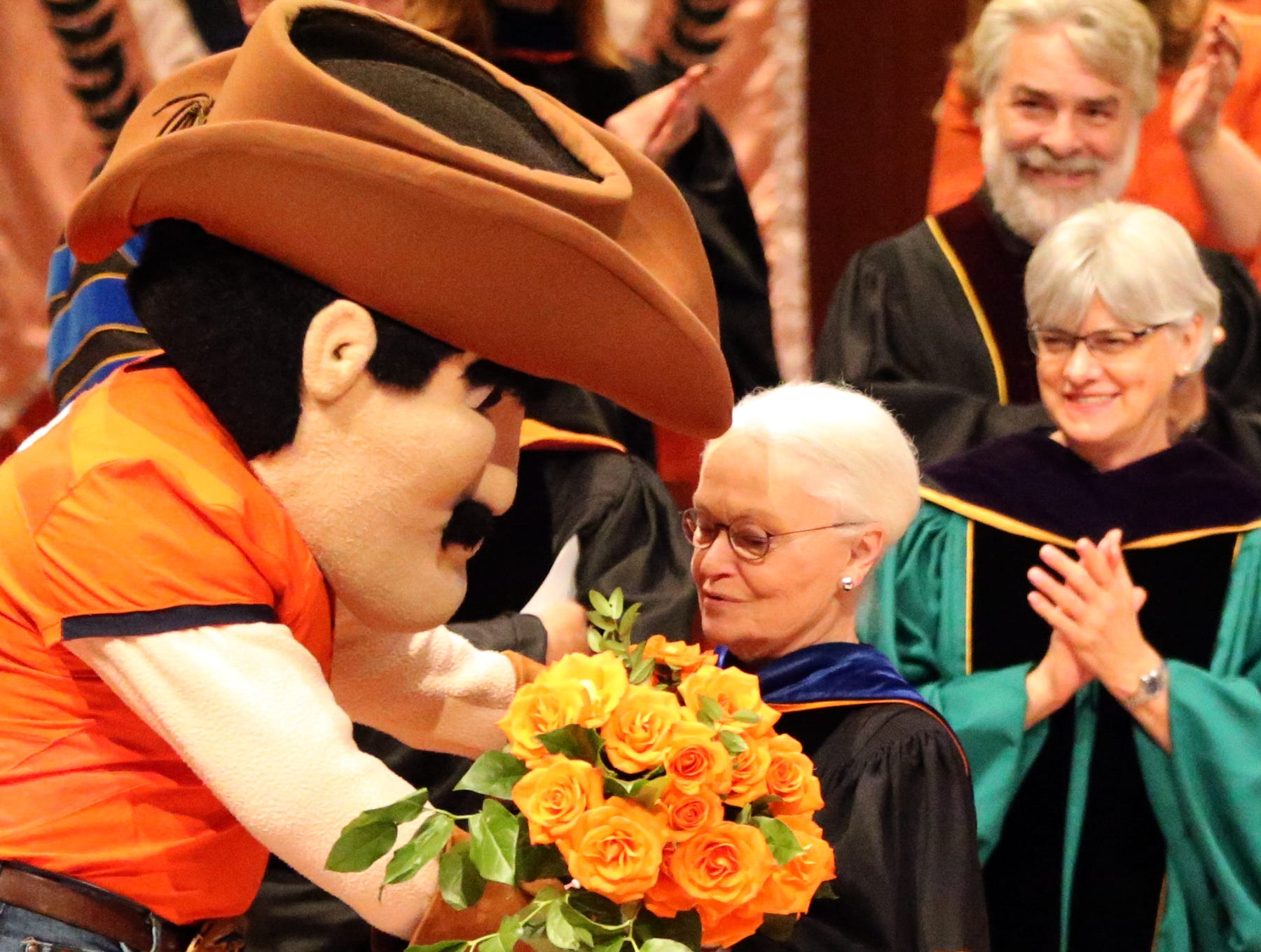 UTEP president Diana Natalicio receives a surprise bouquet of flowers from Paydirt Pete at the end of her remarks during the 2018 Fall Convocation Thursday on campus.