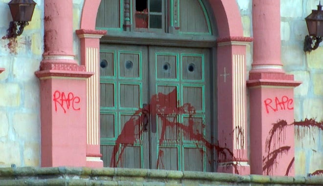 """This Wednesday photo from video provided by KEYT-TV shows historic Old Mission Santa Barbara, where vandals caused some $30,000 damage, splattering it with red paint and spraying """"rape"""" and a misspelled version of the word """"genocide"""" across its stone facade."""