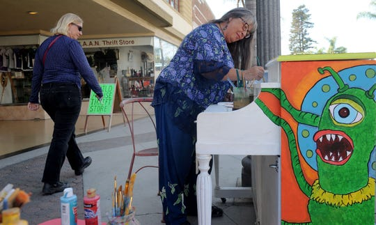 """Local artist Sarah Flesher paints letters on a piano with the theme """"Return to the Forbidden Planet"""" in front of the Child Abuse & Neglect Thrift Store in Ventura."""