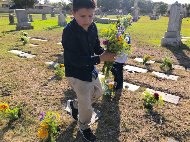 Isaiah Yepez distributes flowers among graves for infants at Santa Clara Cemetery in Oxnard.