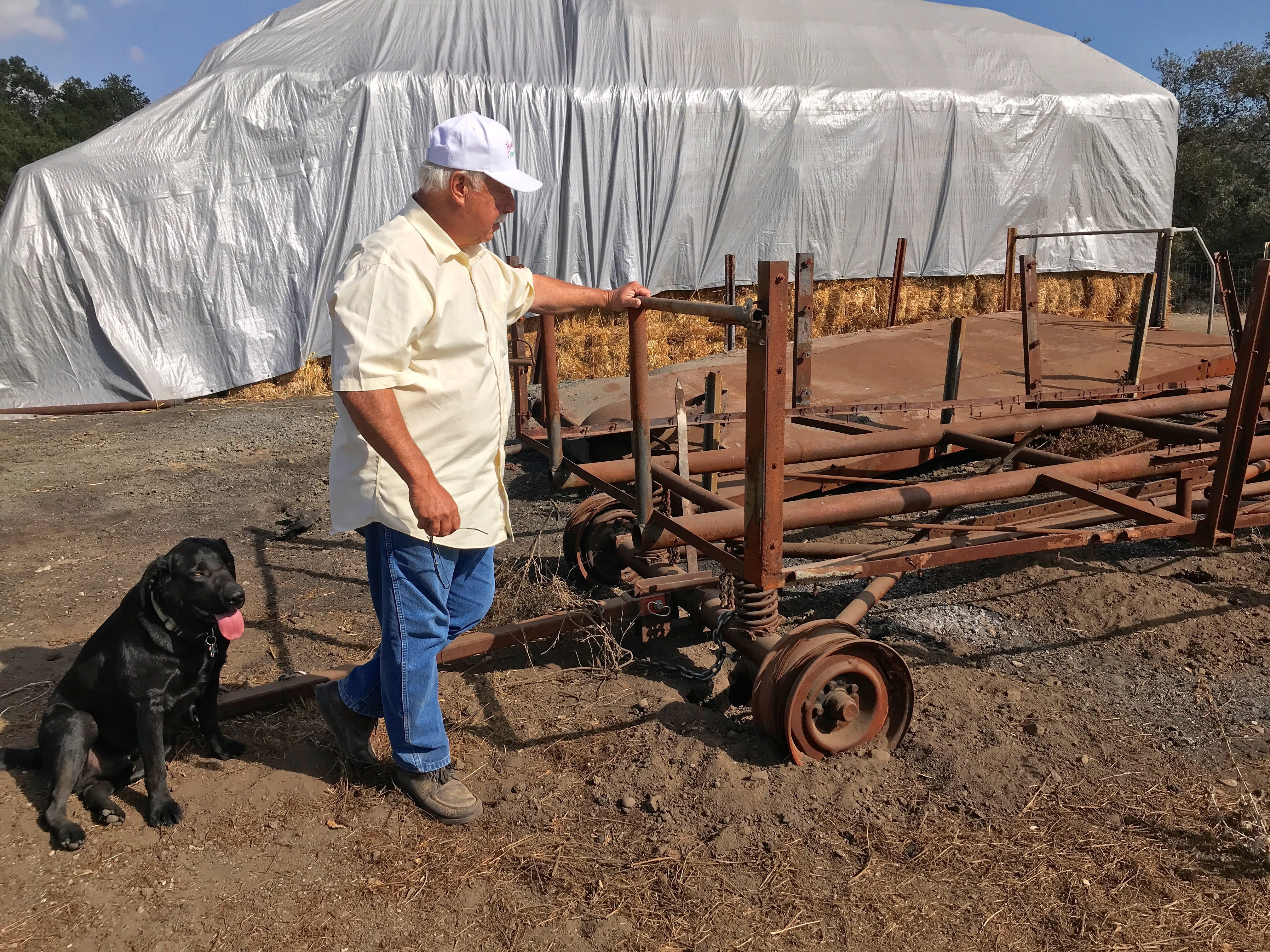 DeWayne Boccali and his dog Buster stand by the remains of two trailers used for the annual haunted hayride. The trailers burned in the Thomas Fire.