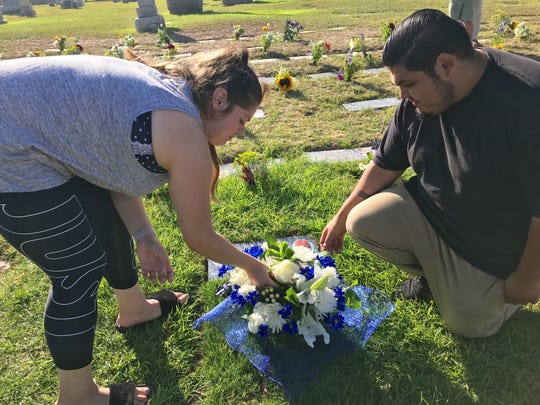 Lexie Suarez and her husband, Victor Lopez, of Oxnard, put flowers on the gravestone of her son, Vin'Cinnt Jesus Lopez. The child was born prematurely at 20 weeks and did not survive.