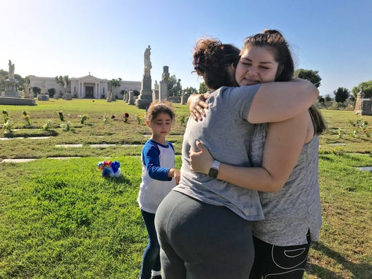 Gabriela Mendoza, left, hugs Lexie Suarez, who lost her son 20 weeks into her pregnancy. Suarez and her husband now help Mendoza place flowers on other infant graves at Santa Clara Cemetery in Oxnard, as well as visiting their own son's grave.