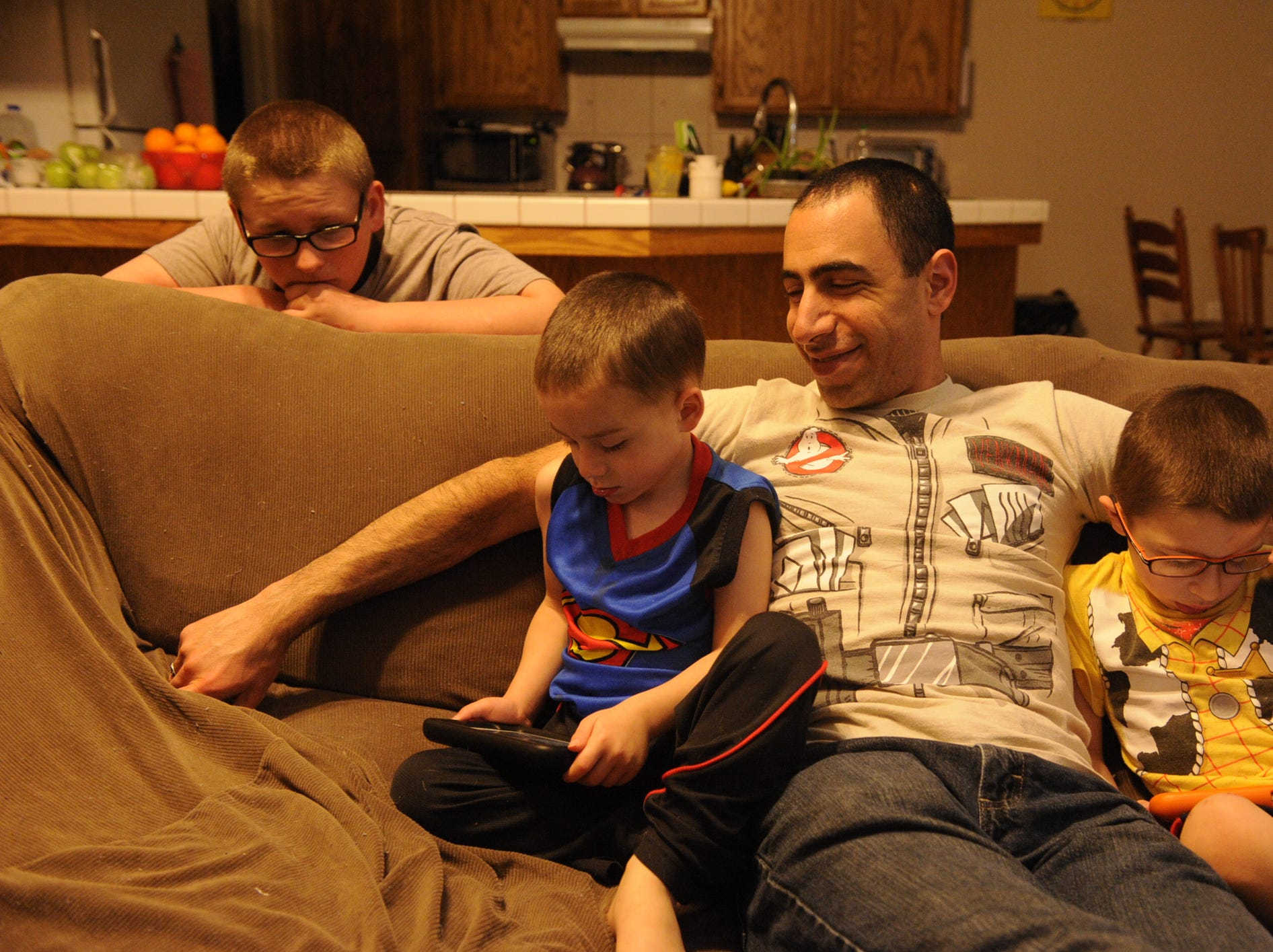 Robert Williams, 13, looks on as his brother Olly Ajluni, 3, plays on a computer with the younger boys' father, David Ajluni, 32. At right is the boys' brother Joey Ajluni, 5. Olly is in remission for Langerhan Cell Histiocytosis (LCH), an autoimmune cancer hybrid disease.