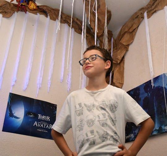 "Ollie Aljuni, now 8-years-old, poses in front of his ""Tree of Souls"" nightlight. Avatar is his favorite movie."