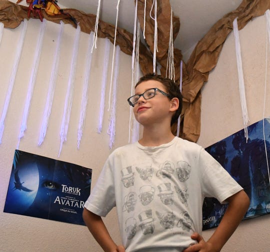 "Ollie Aljuni, now 8-years-old, poses in front of his ""Tree of Souls"" nightlight. Avatar is his favorite movie."