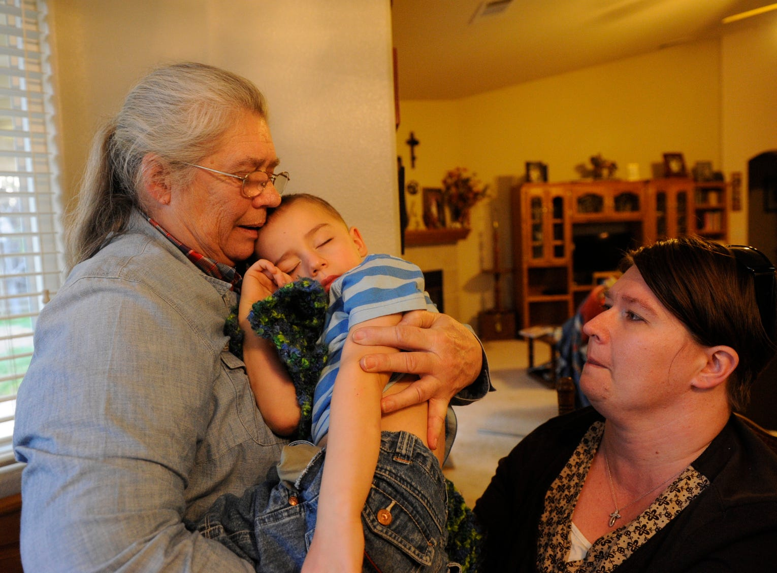 Elizabeth Taft, of Squaw Valley, left, takes her grandson Oliver Ajluni, 3, from her daughter, Shannan Aljuni, after he suffered a seizure. Although he's in remission from a rare autoimmune hybrid disease, he suffers seizures as a side effect from the chemotherapy treatment that saved his life.