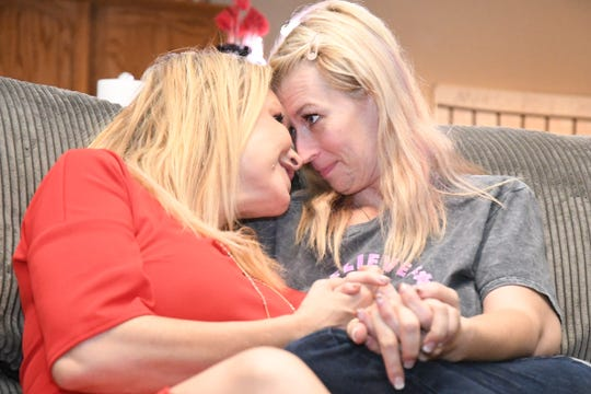 Shannon Ajluni and Face of Cancer founder Holly Carter nuzzle on Aljuni's couch. Their documentary premieres Friday at the Visalia Fox.