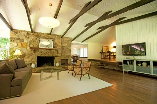 The living room's vaulted beamed ceiling, cantilevered steps and the walls of windows