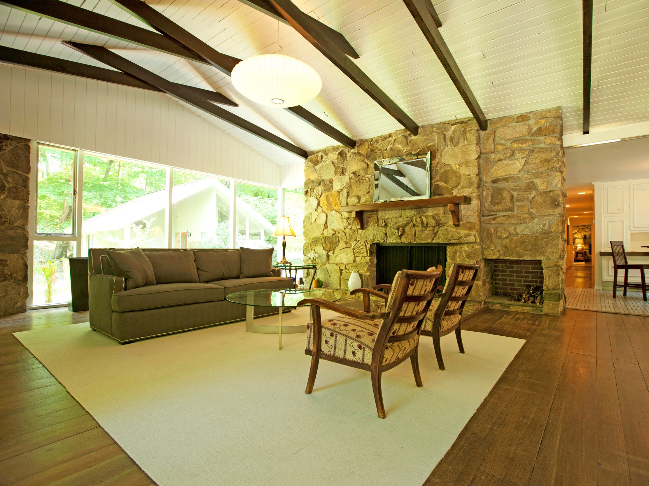 The striking masonry rock wall fireplace is the centerpiece of the open living space.