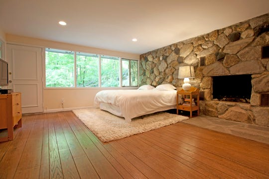 The master bedroom suite features a magnificent stone wall incorporating a wood burning fireplace as a backdrop for peaceful nights.