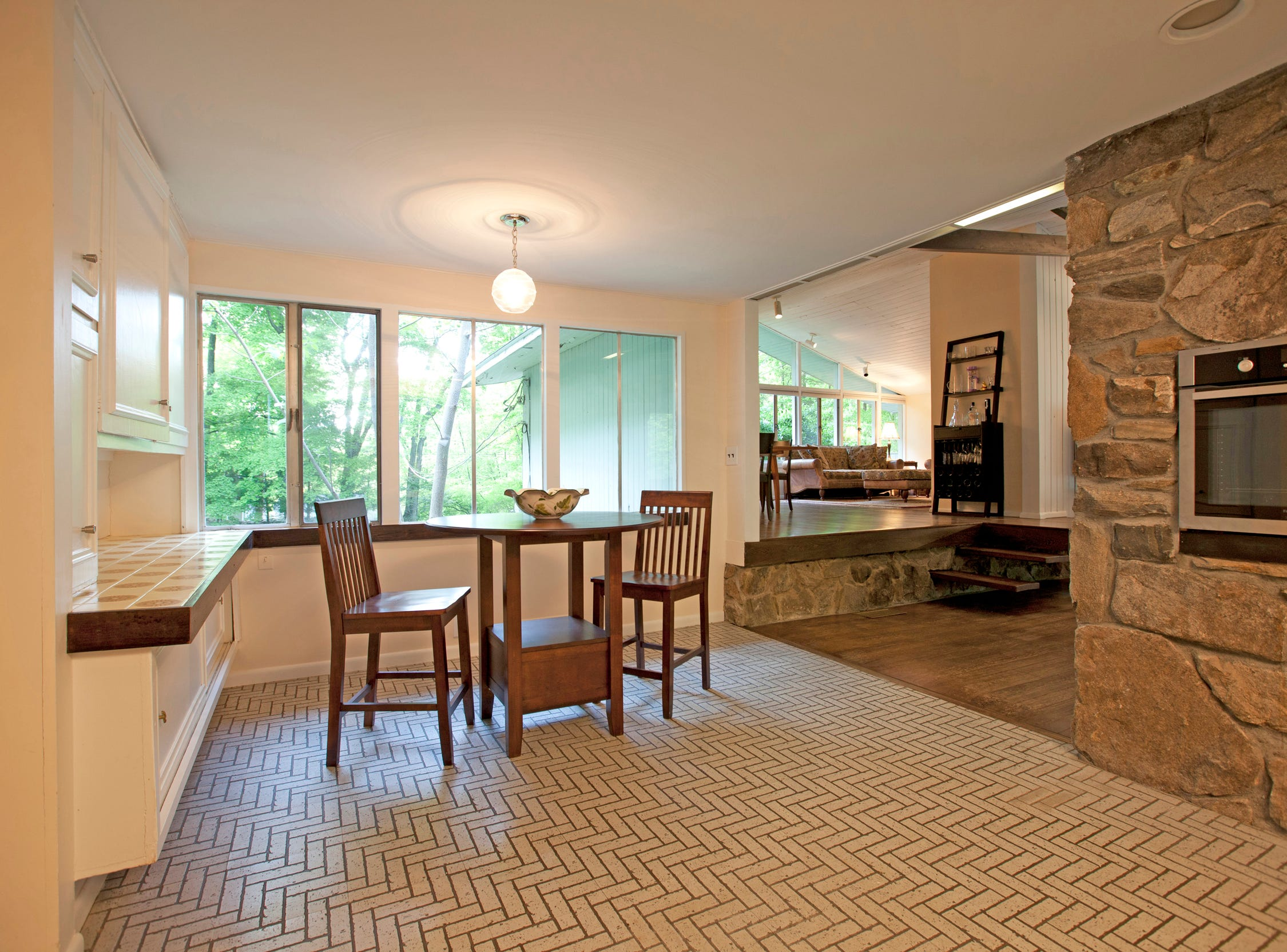 In the kitchen, a built-in stainless steel oven is located within the masonry rock wall.