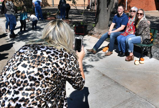 June Seigler and her grandchildren, Matthew McKee and Jessica McKee, have their photograph taken during the dedication ceremony of a bench in memory of the late Ernest Seigler at the Wichita Falls Farmers Market Thursday.