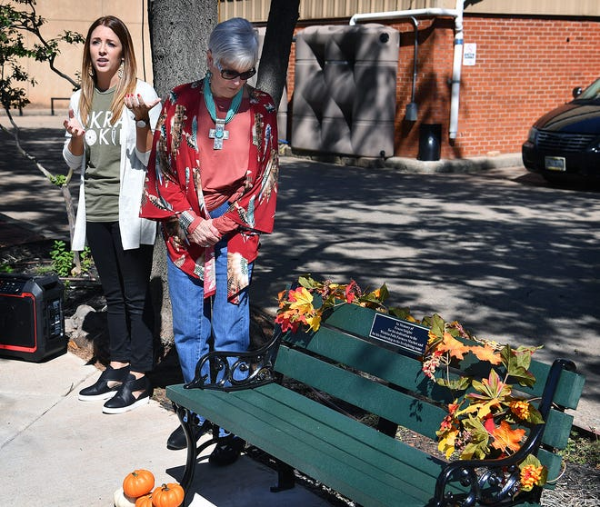 Jana Schmader, left, executive director of Downtown Wichita Falls Development, speaks Thursday afternoon with June Seigler during the dedication ceremony for a bench in memory of her late husband, Ernest Seigler, at the Wichita Falls Farmers Market.