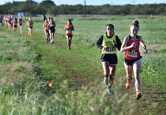 Leah Bullinger of Holliday and Emily Longoria of Henrietta lead the Varsity Girls pack early in the District 8 3-A Cross Country meet Thursday in Holliday.