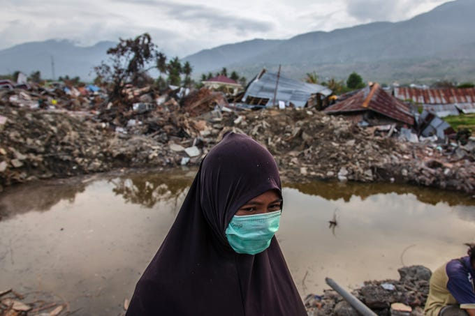 A survivor, Tina, standing in a damaged area waits for news of her daughter Marsha and Keila as they search for victims following the earthquake on Oct. 11, 2018 in Palu, Indonesia. The death toll climbed past 2,045 and officials warn another 5,000 people remain missing and feared buried in mud and rubble.