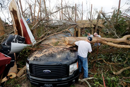 People cut away a tree that'll on a vehicle in the aftermath of Hurricane Michael in Panama City, Fla., Oct. 11, 2018.