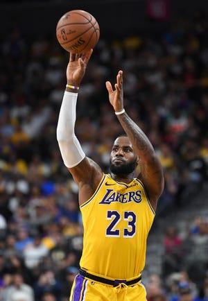 LeBron James hits a three-point shot at the end of the first half against the Warriors.