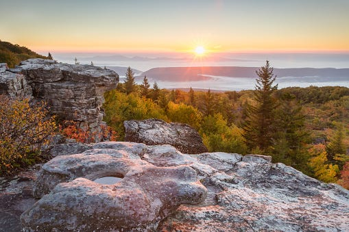 Sun rising against blue sky with mountain tops rising out of the foggy valley below and rock formations and autumn foliage in foreground
