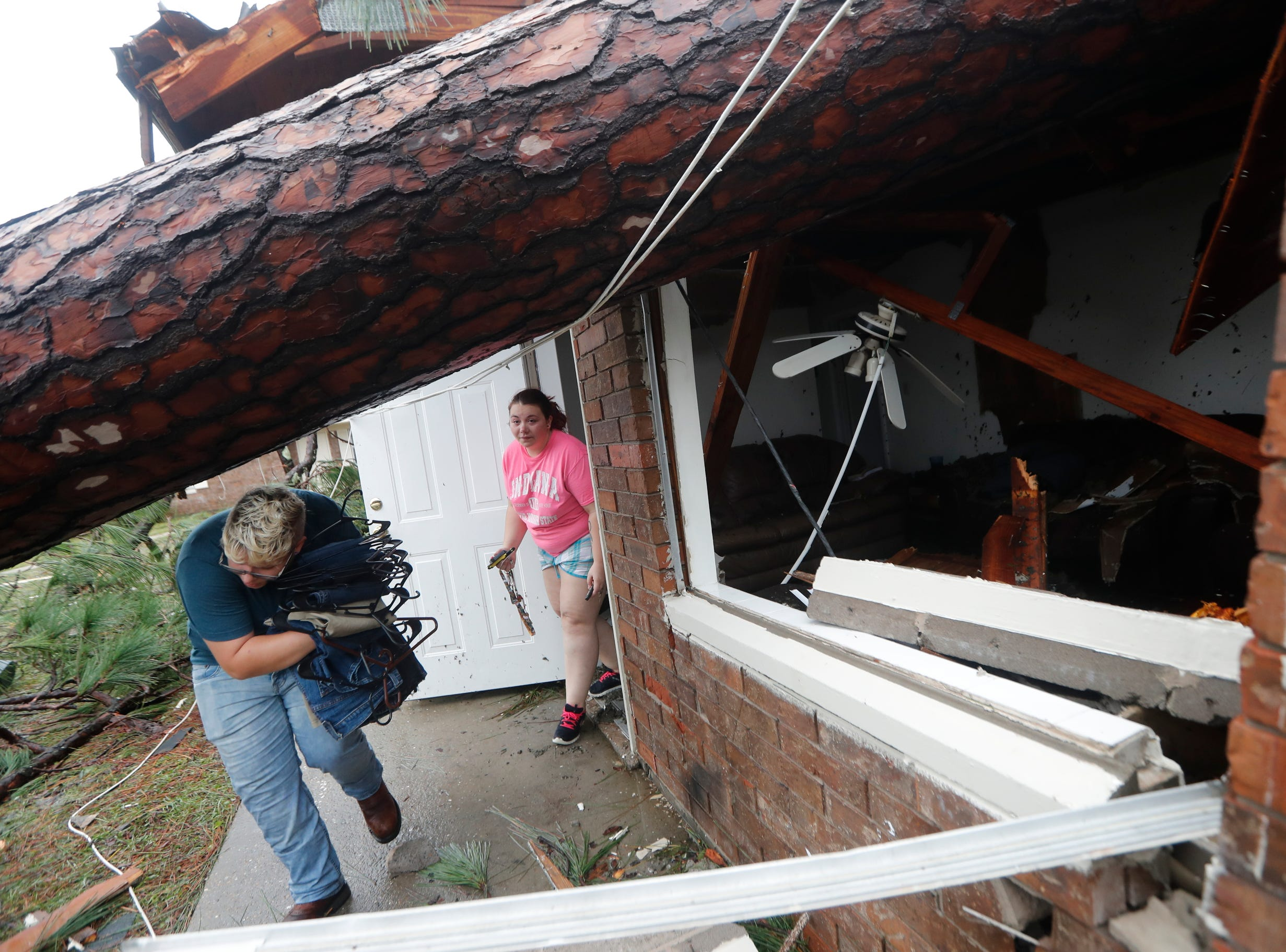 Megan Williams, left, and roommate Kaylee O'Brian take belongings from their destroyed home after several trees fell on the house during Hurricane Michael in Panama City, Fla.,