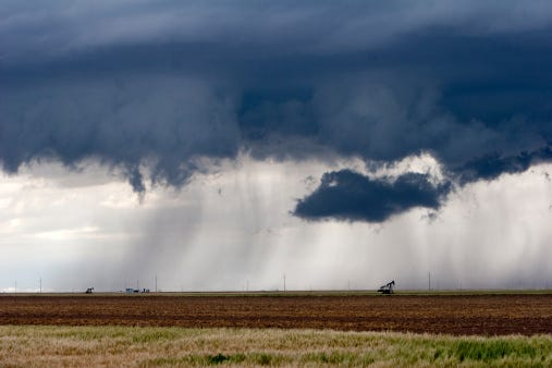 A thunderstorm looms over oil rigs in western Kansas