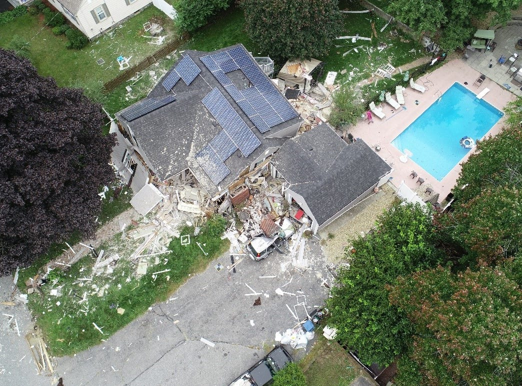 Aerial view of damaged home where a fatality occurred after the chimney collapsed on vehicle in the driveway.