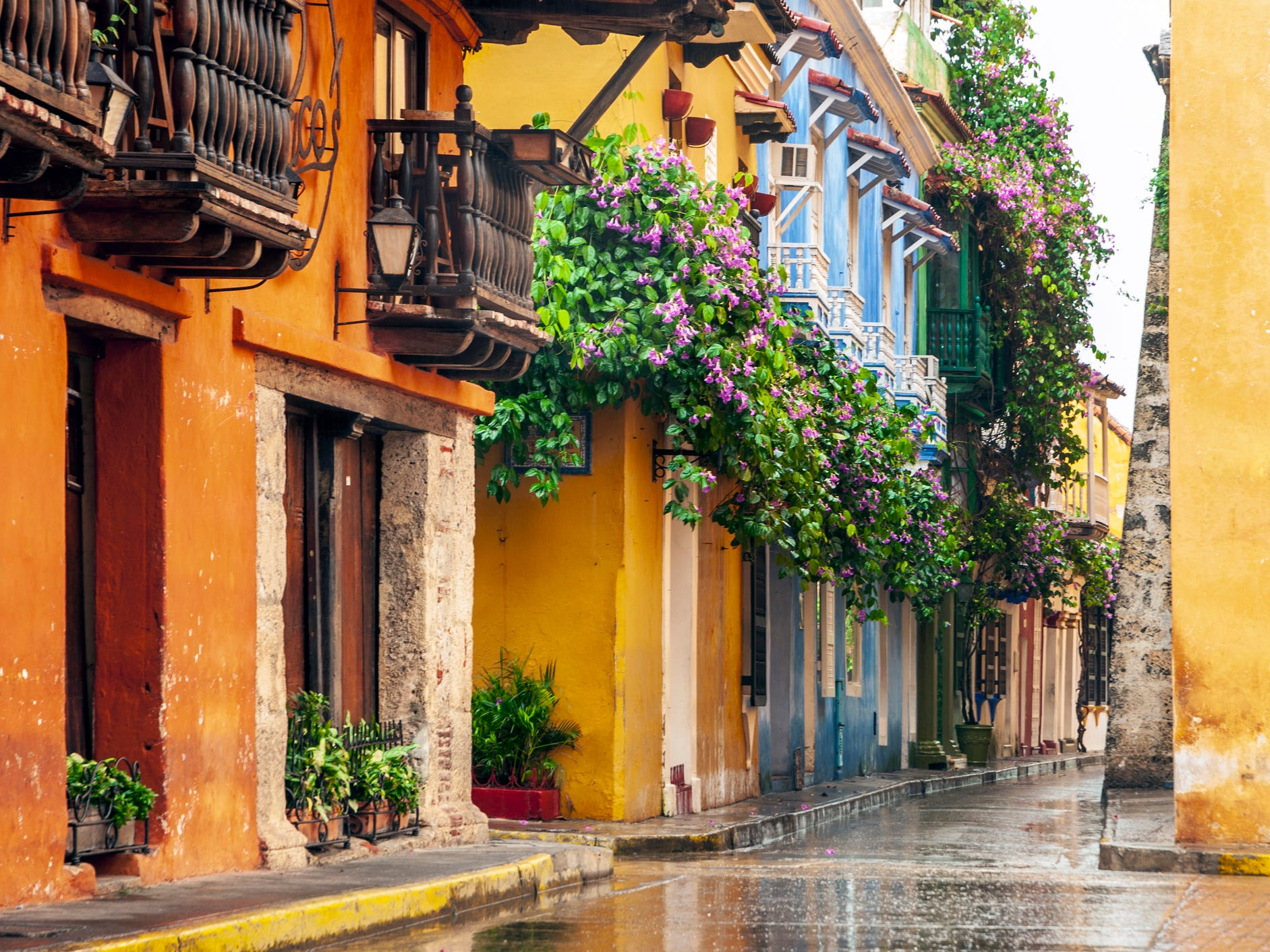 Pink and purple blooms spill out of flowerboxes on wooden balconies, colorful churches loom over sprawling plazas, and the turquoise waters of the Caribbean Sea glimmer in the distance.